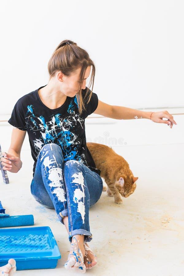 Концепция людей, реновации и ремонта - портрет прекрасной молодой женщины с котом делая redecoration в квартире стоковые фото