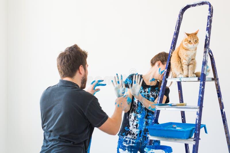 Концепция людей, реновации и ремонта - портрет прекрасных пар с котом делая redecoration в квартире стоковые изображения