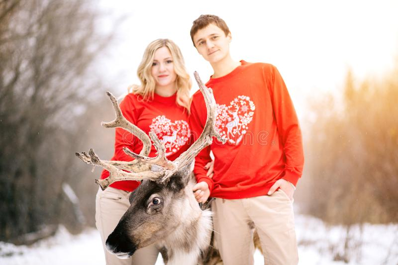 Концепция людей, сезона, влюбленности и отдыха - счастливая пара обнимая и смеясь над outdoors в зиме Фокус на оленях стоковые изображения