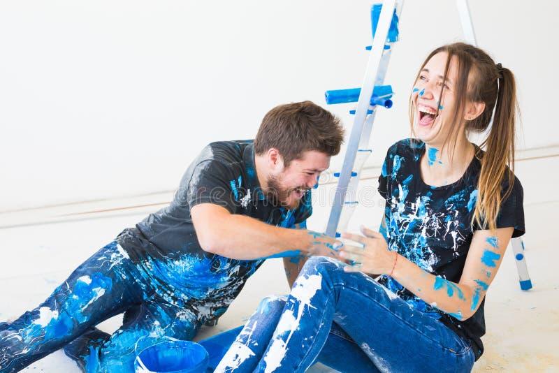 Концепция людей, redecoration и отношения - молодая смешная пара делая реновацию в новой квартире и иметь потеху на стоковое изображение
