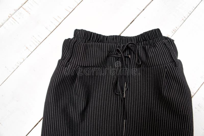 Концепция моды одежд Деталь черных брюк на белой деревянной предпосылке r стоковые изображения