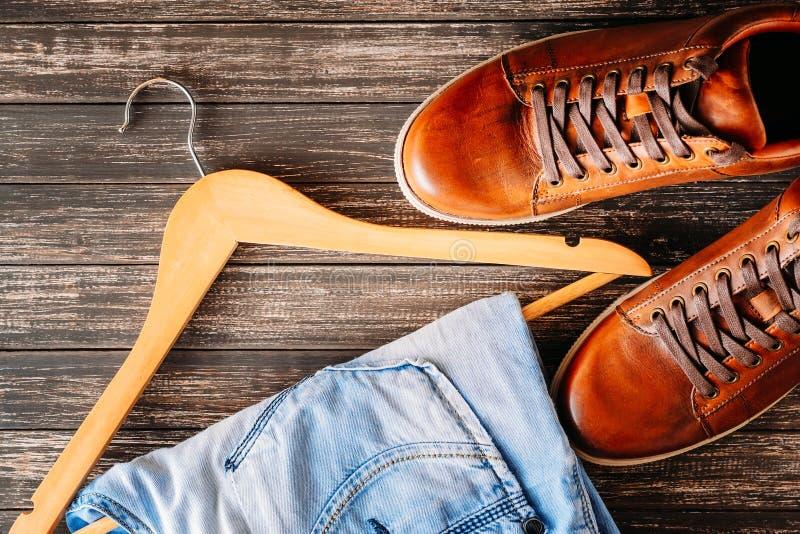 Концепция моды человека Мужские случайные кожаные коричневые ботинки, джинсы и вешалка на темной предпосылке стоковое фото rf