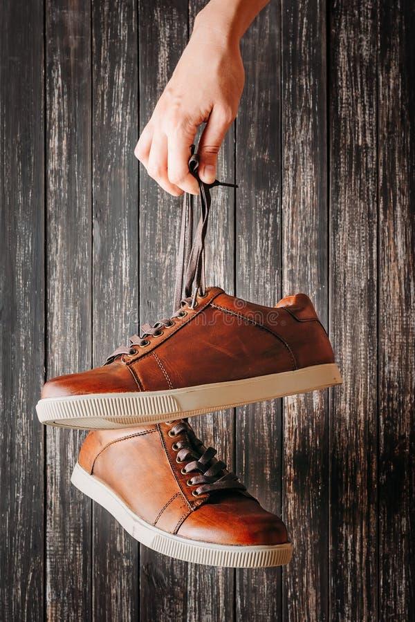 Концепция моды человека Рука держит для ботинок шнурков коричневых кожаных мужских на темной предпосылке стоковые изображения rf