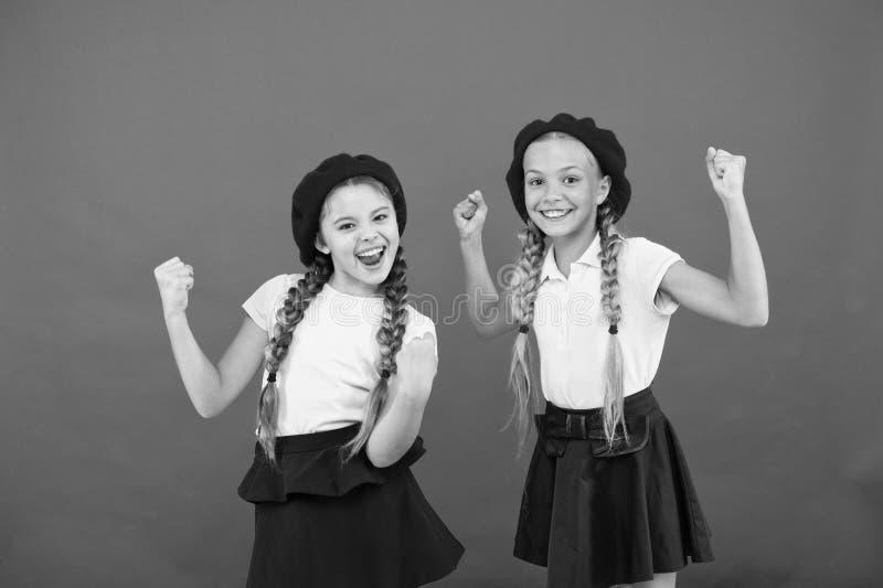 Концепция моды школы Девушки зрачка усмехаясь носят официальные шляпы формы и берета Международная программа школы обменом стоковые изображения