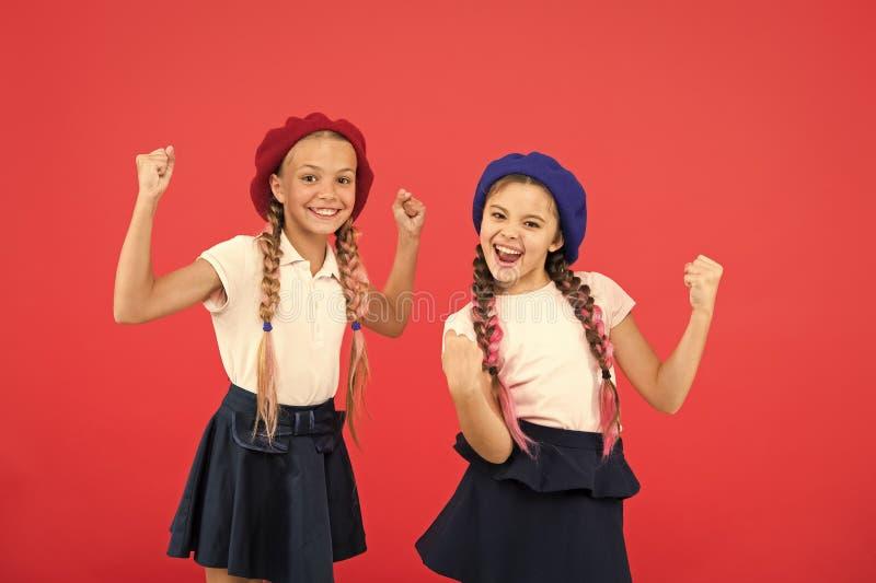 Концепция моды школы Девушки зрачка усмехаясь носят официальные шляпы формы и берета Международная программа школы обменом стоковое изображение rf