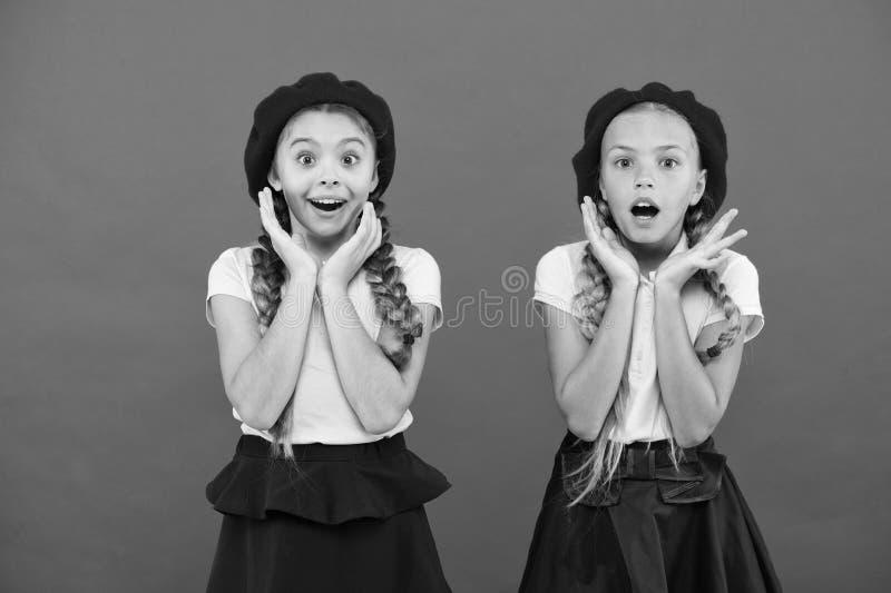 Концепция моды школы Удивленные девушки носят официальную равномерную красную предпосылку Международная программа школы обменом стоковое изображение