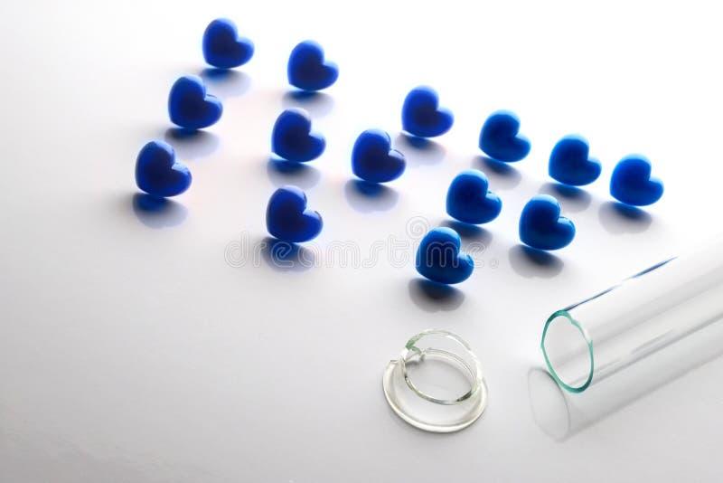 Концепция неудачного in vitro землеудобрения Abriveura IVF от голубых сердец и сломленной пробирки на переднем плане стоковое изображение