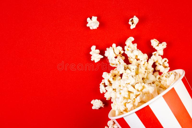 Концепция ночи кино - попкорн, стекла, яркая красная предпосылка стоковые изображения