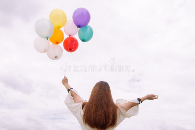 Концепция образа жизни женщины - рука женщины держа пук покрашенных воздушных шаров с голубым небом Винтажный стиль цвета фильтра стоковое фото rf