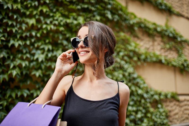 Концепция образа жизни Закройте вверх привлекательной молодой темн-с волосами кавказской женщины в солнечных очках и черном усмех стоковое изображение