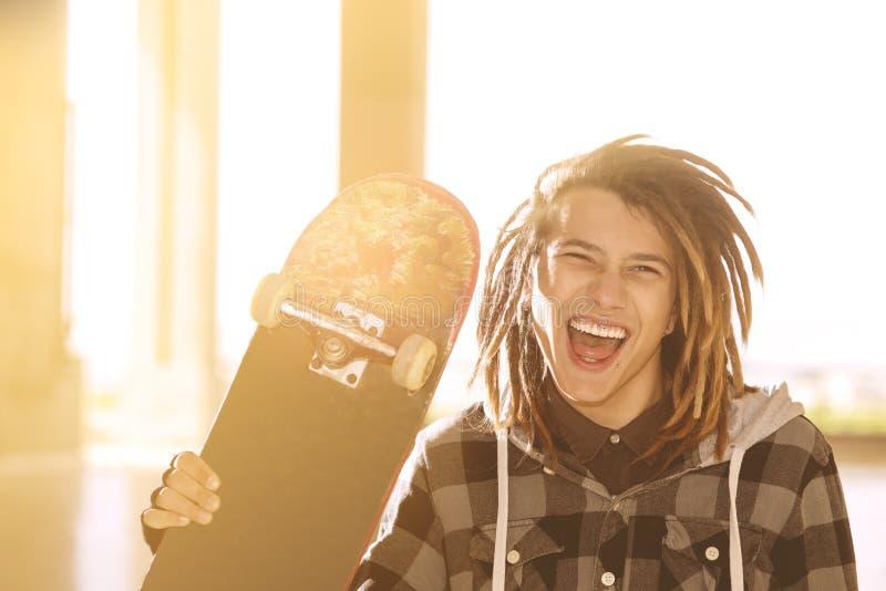 Концепция образа жизни молодого парня с скейтбордом и волосами w rasta стоковые фотографии rf