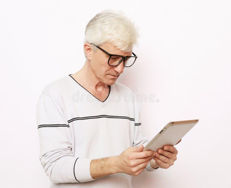 Концепция образа жизни, tehnology и людей: Счастливый старший человек используя цифровую таблетку стоковые изображения