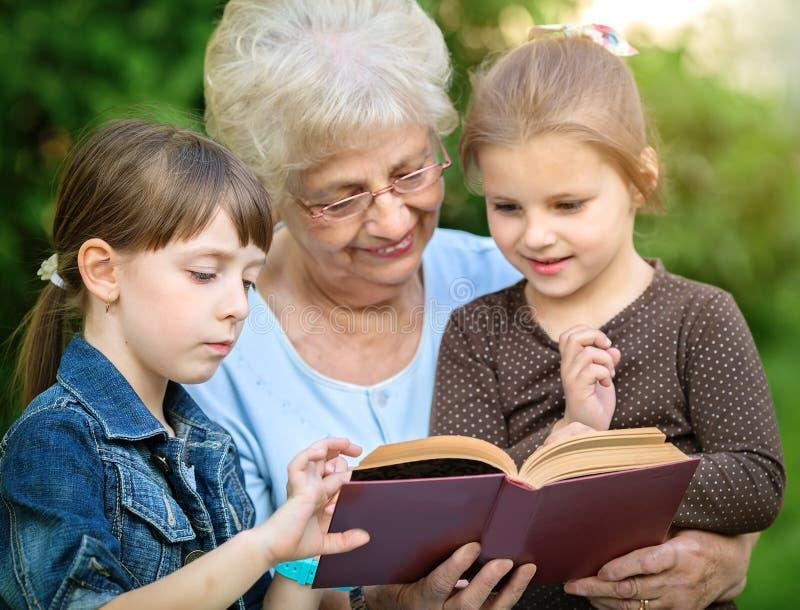 Концепция образования, бабушка читая книгу для внуков стоковое фото