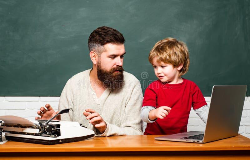 Концепция образования и преподавательства Зрачки учителя помогая изучая на столах в классе r Начальная школа стоковое фото