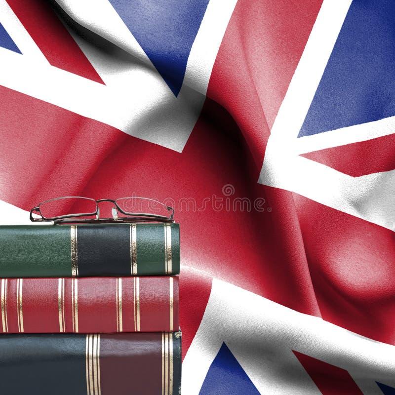 Концепция образования - стог книг и стекел чтения против национального флага Великобритании стоковые изображения