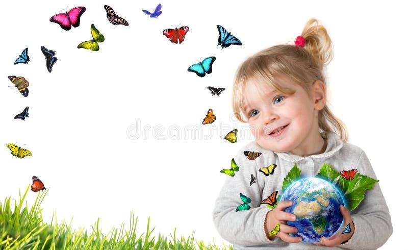 Концепция окружающей среды, ребенок держа землю с бабочками летания стоковая фотография