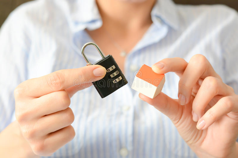 Концепция домашней безопасности или страхования с замком шифра держала кроме миниатюрного дома стоковая фотография