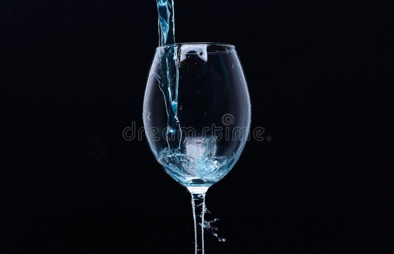 Концепция освежающего напитка Коктеиль с голубой жидкостью в стекле Стекло при открытое море лить с жидкостью с брызгает стоковое изображение