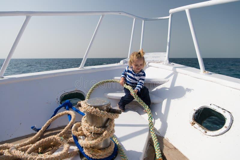 Концепция отключения моря Малый ребенк наслаждается отключением моря на шлюпке Матрос мальчика на отключении моря Отключение и кр стоковые фото