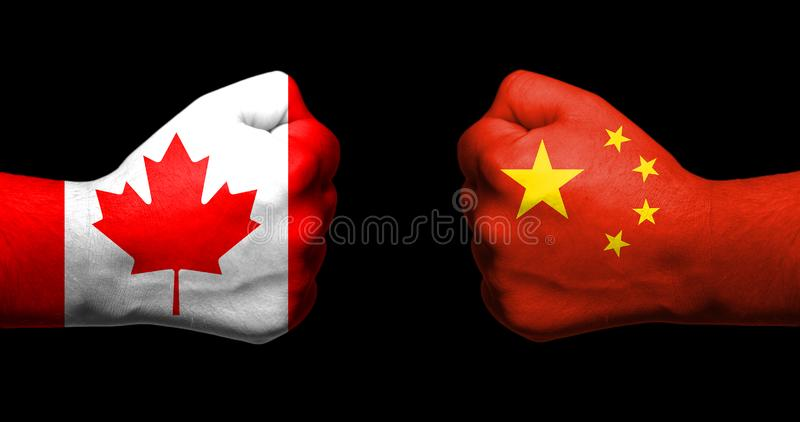 Концепция отношений/конфликта между Канадой и Китаем символизированного 2 сопротивляемыми сжатыми кулаками стоковая фотография rf