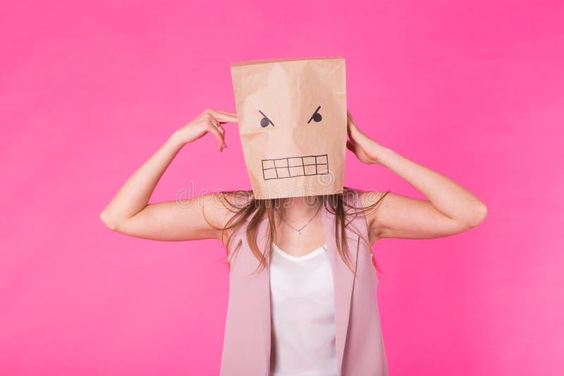 Концепция отрицательных эмоций - сердитая женщина с бумажной сумкой на его стороне стоковые фото
