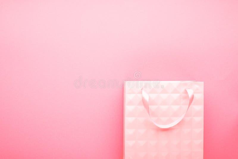 Концепция пакета подарка Предпосылка подкрашивана в одном цвете, бумажном мешке и основание розово горизонтально скопируйте космо стоковое изображение