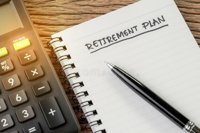 Концепция пенсионного плана, калькулятор с пустым блокнотом с ручкой и заголовок почерка как пенсионный план на деревянной таблиц стоковая фотография rf