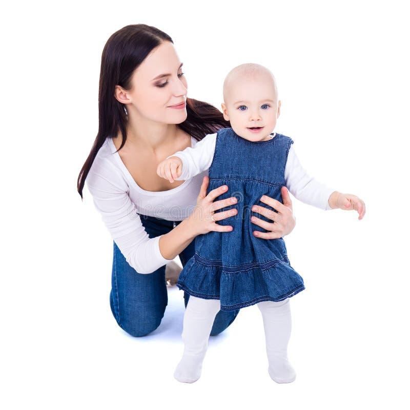 Концепция первого шага - счастливая молодая мать играя с меньшим daug стоковые изображения