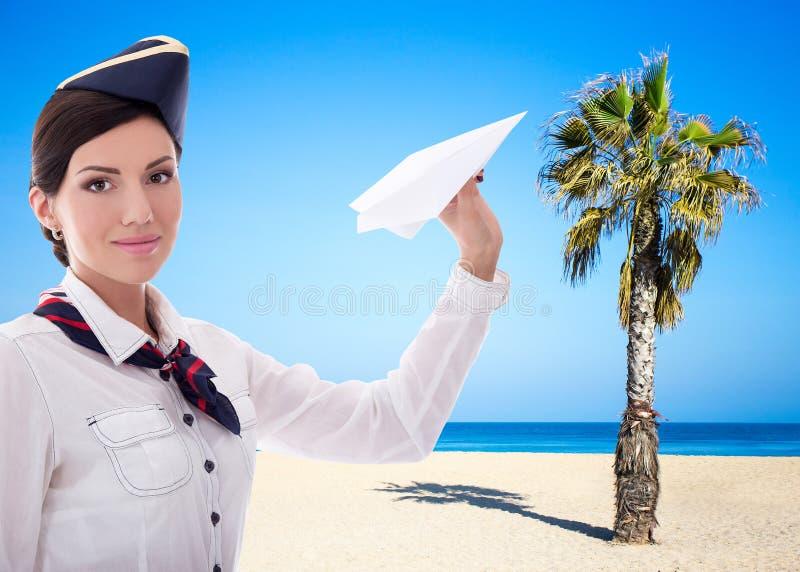 Концепция перемещения и лета - stewardess с самолетом бумаги над предпосылкой пляжа стоковые изображения rf