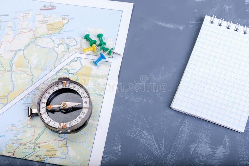 Концепция перемещения - компас на карте, pushpin и блокноте стоковая фотография rf