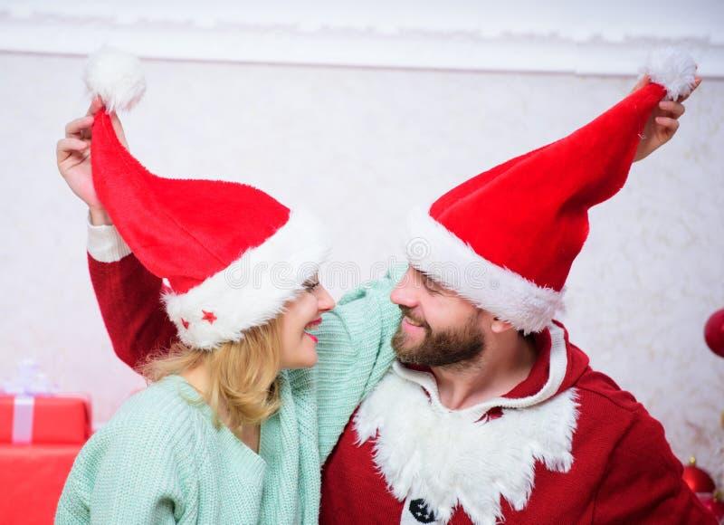 Концепция подарка рождества Пары в любов наслаждаются торжеством рождества Пары носят шляпы как рождественская елка Санта Клауса стоковое фото