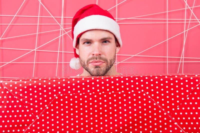 Концепция подарка рождества Санта приносит подарок для вас Человек привлекательный Санта Клаус носит большую коробку Подготавлива стоковое изображение
