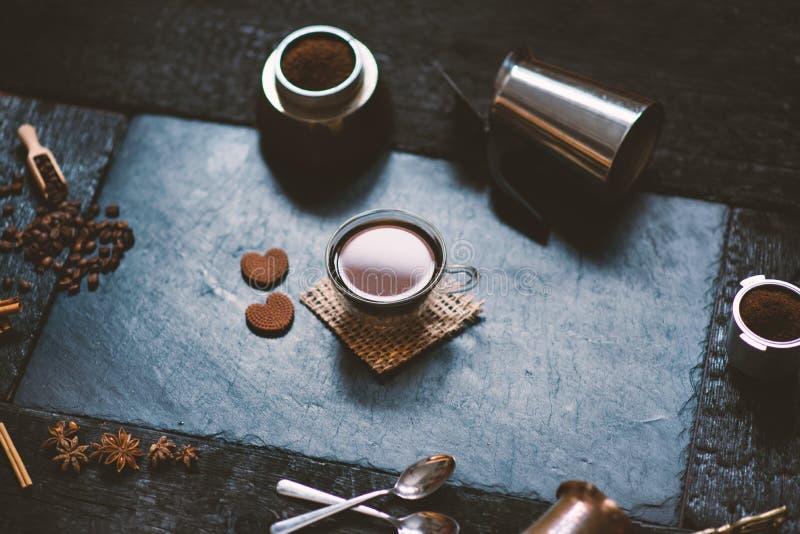 Концепция - подготовка кофе Кофейная чашка, mocha, кофеварка, зажаренные в духовке фасоли, ложки, cezve turkisch, печенья и карда стоковые изображения