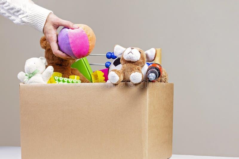 Концепция пожертвования Женщина собирая коробку пожертвования с одеждами, игрушками и книгами стоковые изображения rf