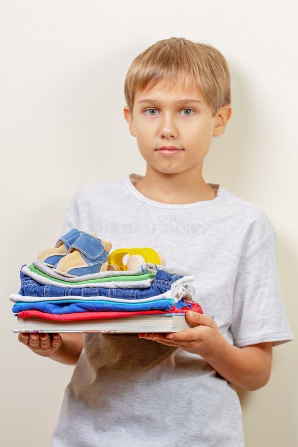 Концепция пожертвования Ребенк держа в его книгах, одеждах и игрушках рук для призрения стоковые фотографии rf