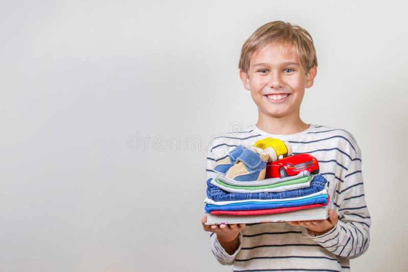 Концепция пожертвования Ребенк держа в его книгах рук, одежды и игрушки для дарят стоковые фото