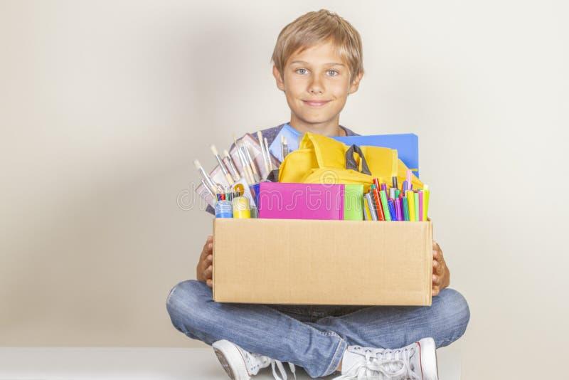 Концепция пожертвования Удержание ребенк дарит коробку с книгами, карандашами и школьными принадлежностями стоковая фотография rf