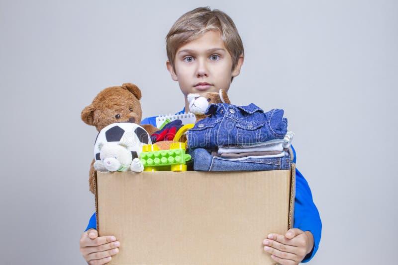 Концепция пожертвования Удержание ребенк дарит коробку с одеждами, книгами, школьными принадлежностями и игрушками стоковые изображения