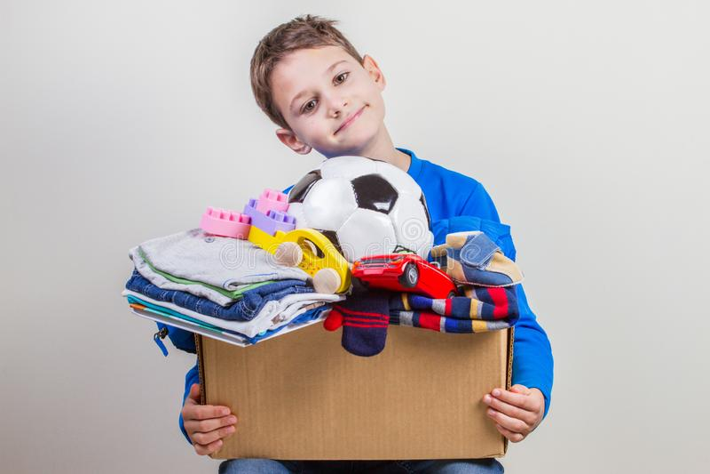 Концепция пожертвования Удержание ребенк дарит коробку с одеждами, книгами и игрушками стоковые изображения