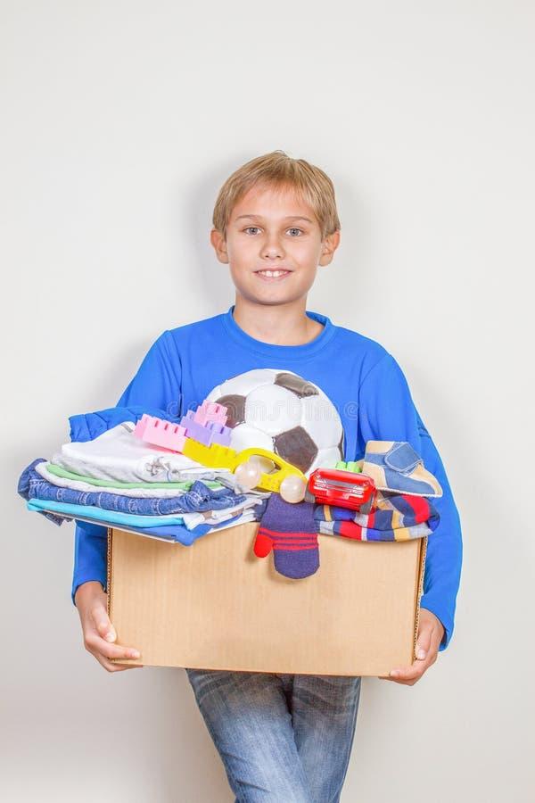 Концепция пожертвования Удержание ребенк дарит коробку с одеждами, книгами и игрушками стоковые фото