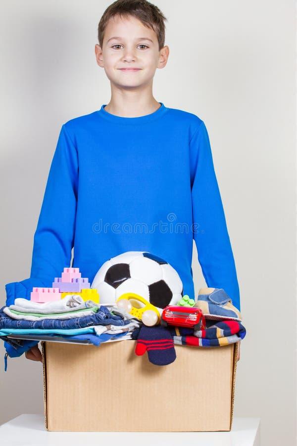 Концепция пожертвования Удержание ребенк дарит коробку с одеждами, книгами и игрушками стоковое фото