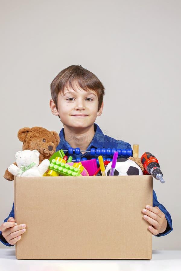 Концепция пожертвования Удержание ребенк дарит коробку с одеждами, книгами и игрушками стоковые фотографии rf