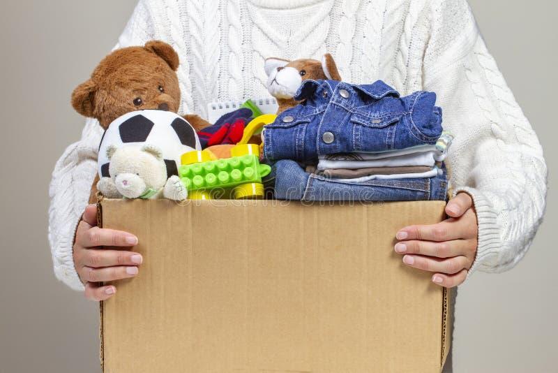 Концепция пожертвования Удержание рук женщины дарит коробку с одеждами, книгами, школьными принадлежностями и игрушками стоковые фотографии rf