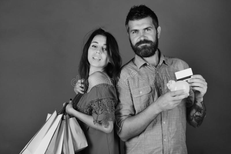 Концепция покупок и свободного времени Пара в влюбленности держит хозяйственные сумки на зеленой предпосылке стоковое фото