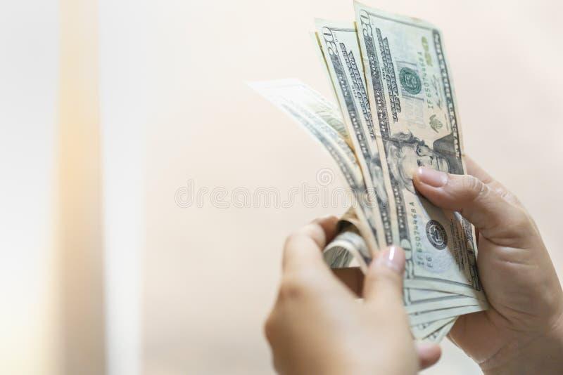 Концепция покупок и сохранения дела денег Закройте вверх удерживания руки женщины и считать банкноту доллара США с космосом экзем стоковое фото rf
