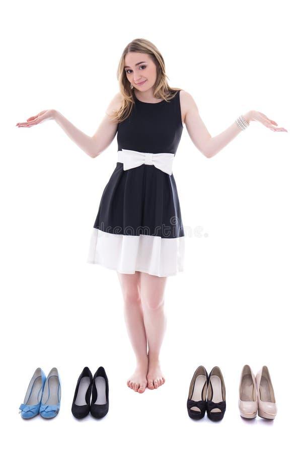 Концепция покупок - красивая женщина выбирая ботинки изолированные на wh стоковое изображение