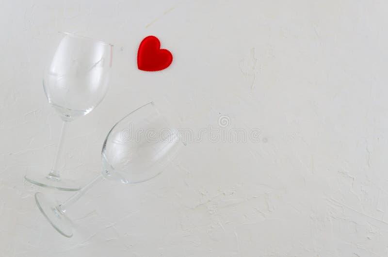 Концепция положенная квартирой романтичная с 2 бокалами и красным сердцем на белой изолированной предпосылке Космос для поздравит стоковое фото rf