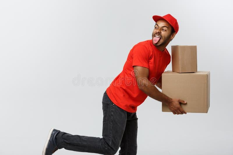 Концепция поставки - красивая Афро-американская спешка работника доставляющего покупки на дом бежать для поставлять пакет для кли стоковые фото