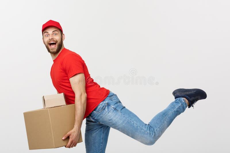 Концепция поставки - красивая кавказская спешка работника доставляющего покупки на дом бежать для поставлять пакет для клиента Из стоковое изображение rf