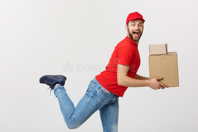 Концепция поставки - красивая кавказская спешка работника доставляющего покупки на дом бежать для поставлять пакет для клиента Из стоковые фотографии rf